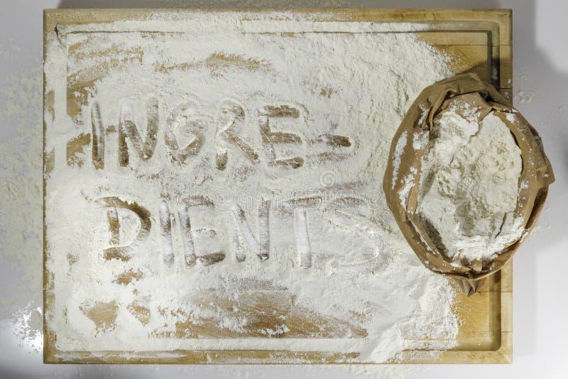 Placa de corte com farinha e ingredientes que escreve no branco imagens de stock royalty free