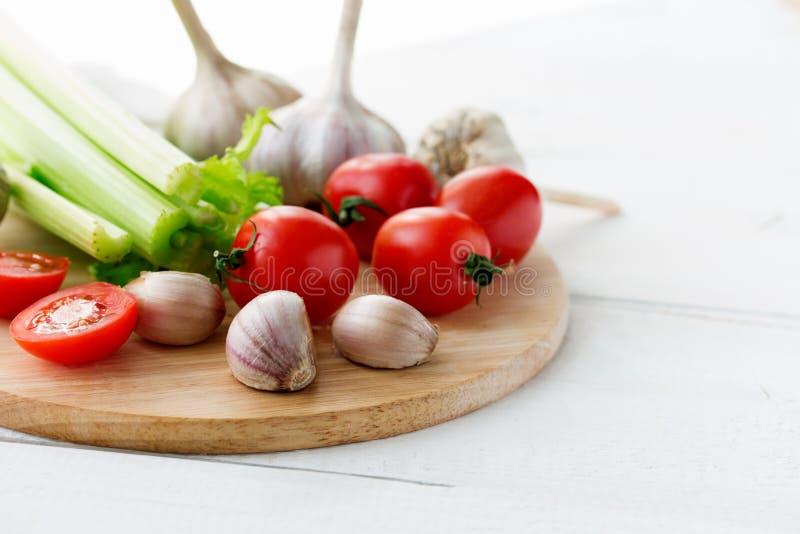 Placa de corte com os legumes frescos na tabela de madeira branca Copyspace fotos de stock