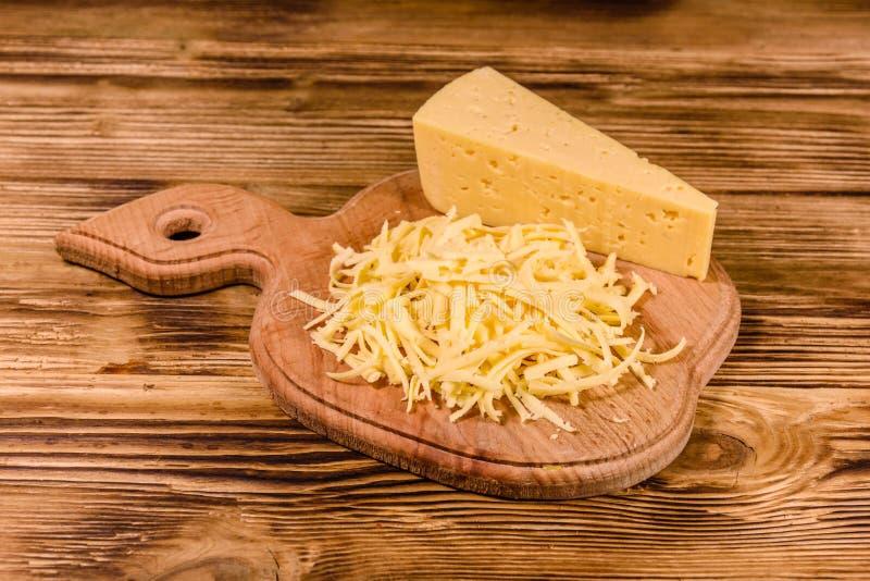 Placa de corte com queijo raspado na tabela de madeira imagem de stock royalty free