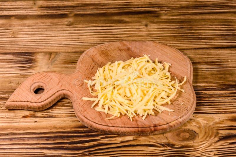 Placa de corte com queijo raspado na tabela de madeira foto de stock royalty free