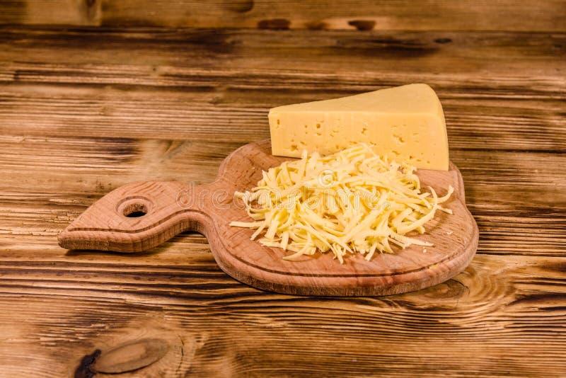 Placa de corte com queijo raspado na tabela de madeira foto de stock