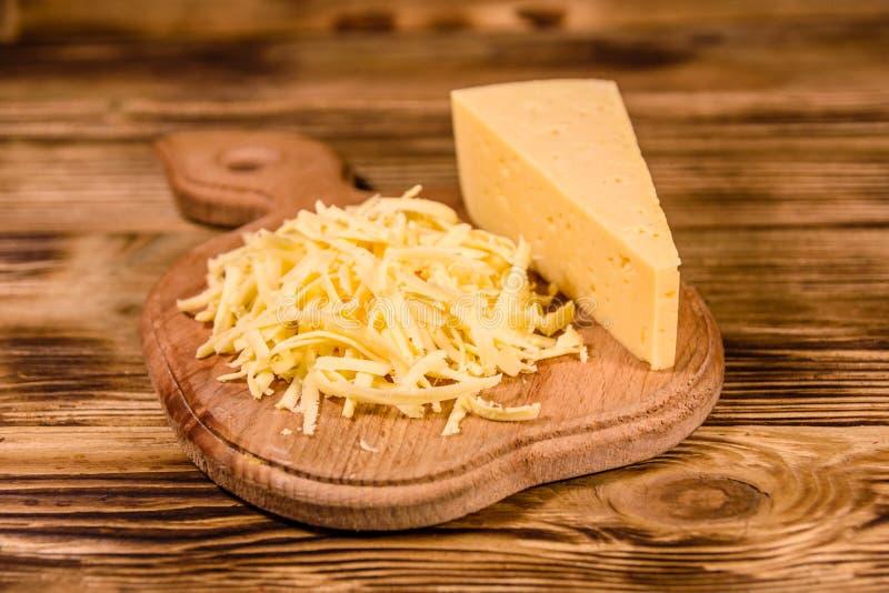Placa de corte com queijo raspado na tabela de madeira fotografia de stock