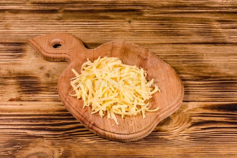 Placa de corte com queijo raspado na tabela de madeira imagens de stock royalty free