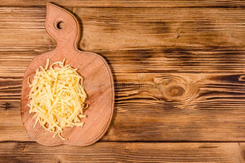 Placa de corte com queijo raspado na tabela de madeira Vista superior fotografia de stock royalty free