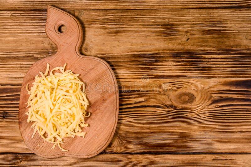 Placa de corte com queijo raspado na tabela de madeira Vista superior foto de stock