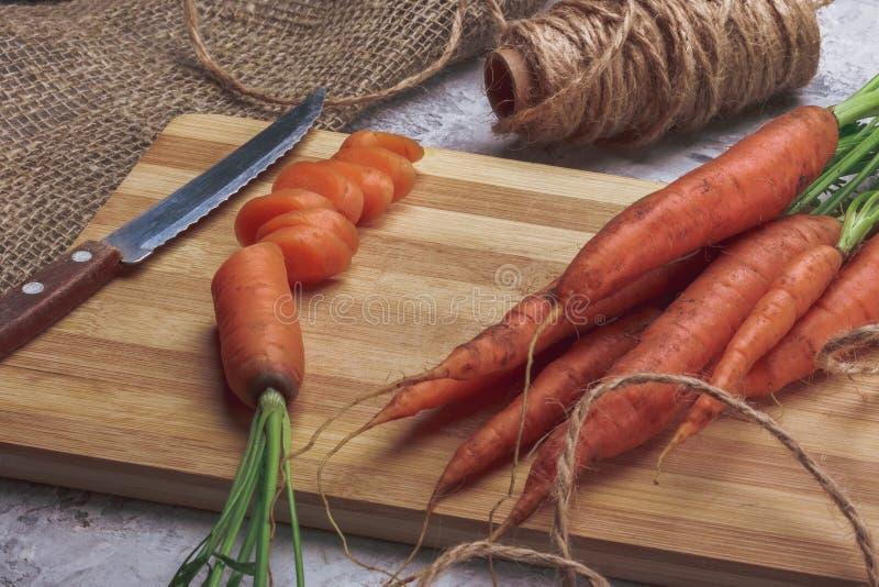 Placa de corte com uma faca e umas cenouras frescas imagem de stock royalty free