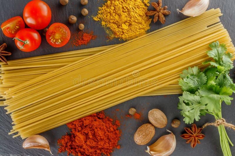Placa de corte da ardósia Especiarias dos espaguetes da composição para cozinhar pratos italianos foto de stock royalty free