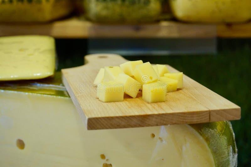 Placa de corte do queijo com os cubos do queijo holandês sobre um bloco da roda do queijo imagens de stock royalty free