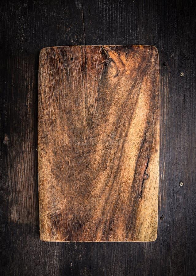 Placa de corte escura velha na tabela de madeira marrom imagens de stock royalty free