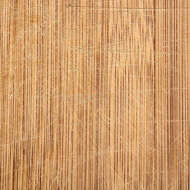 Placa de corte de madeira de bambu macro da grão com as marcas da faca, usadas bem na cozinha fotografia de stock