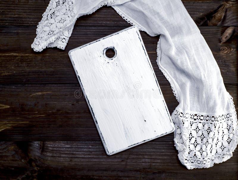 Placa de corte de madeira branca vazia velha e uma toalha de cozinha branca imagens de stock