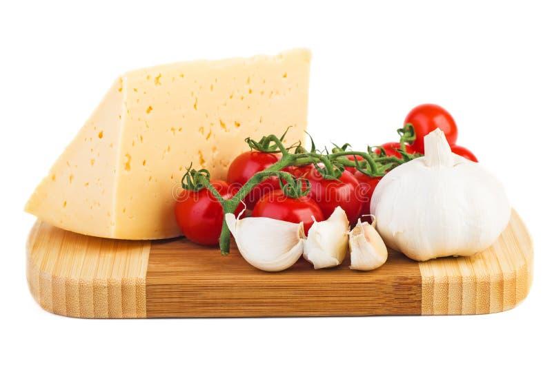 Placa de corte de madeira com tomates frescos, parte de queijo e alho imagem de stock royalty free