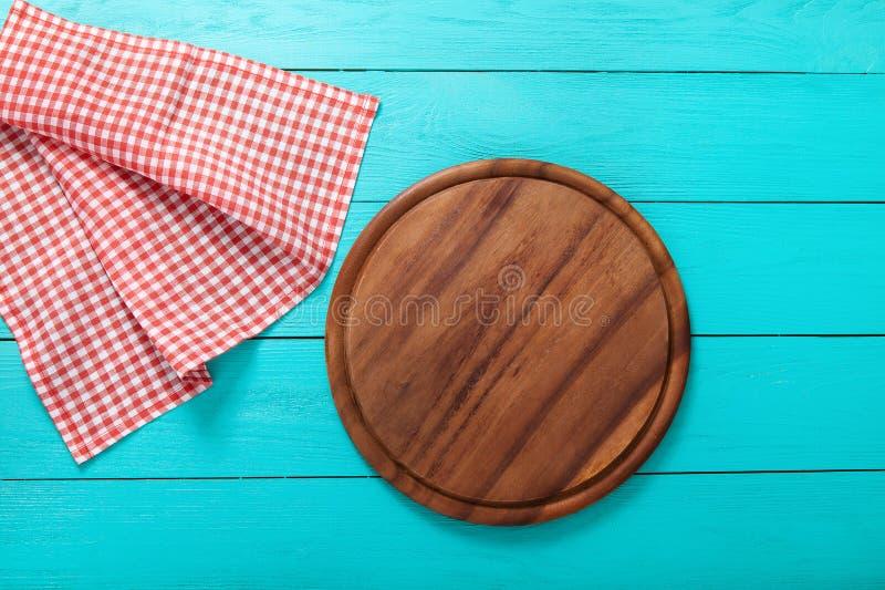 Placa de corte redonda de Brown para a pizza na toalha de mesa vermelha da manta Tabela de madeira azul no restaurante Copie o es foto de stock royalty free