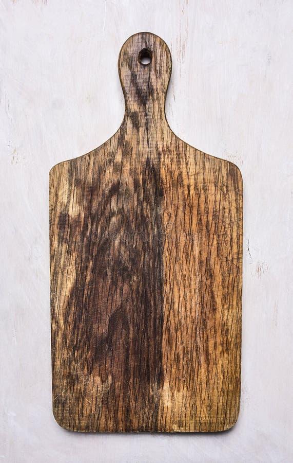 Placa de corte velha em uma beira branca do fundo, lugar do vintage para o fim rústico de madeira da opinião superior do fundo do foto de stock