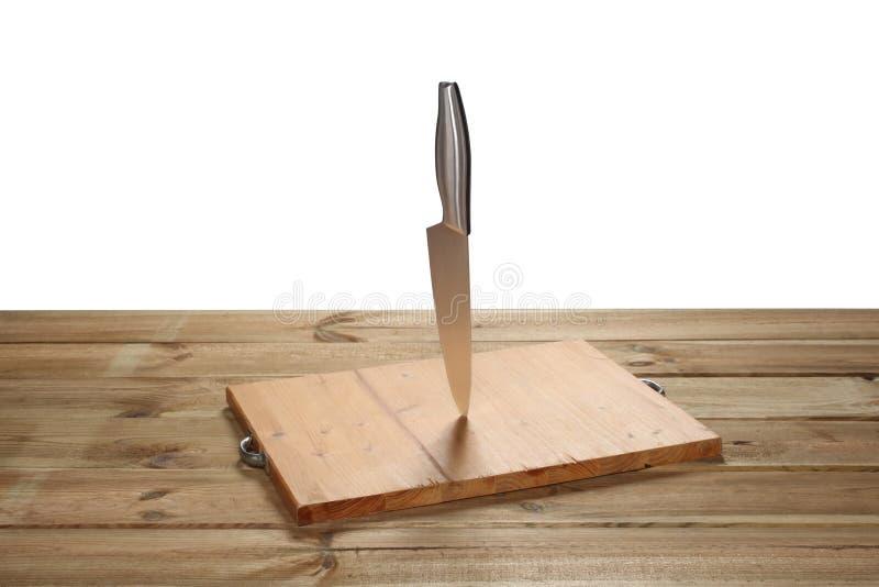 Placa de desbastamento em uma tabela de madeira com uma faca isolada no fundo branco com trajeto de grampeamento e espaço da cópi fotografia de stock