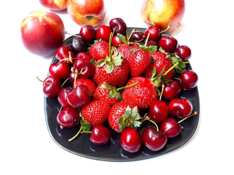 Placa de fresas y de cerezas fotos de archivo