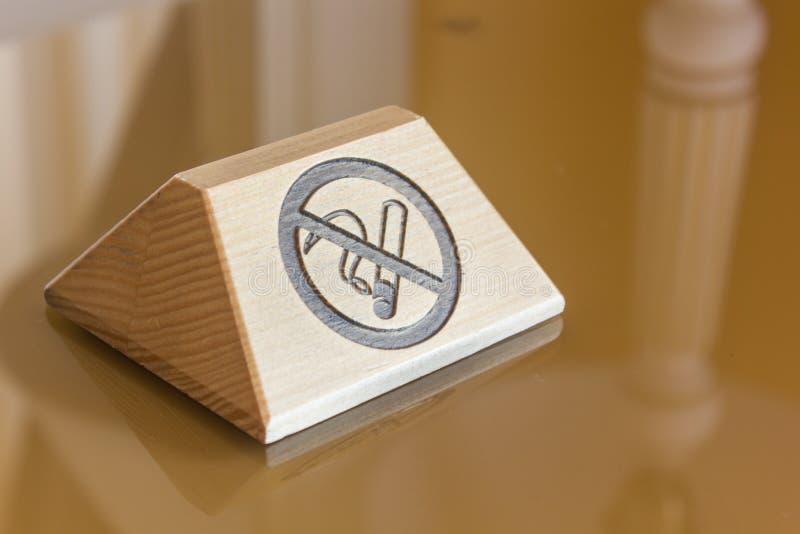 A placa de identificação com não fumadores assina sobre a tabela fotografia de stock royalty free