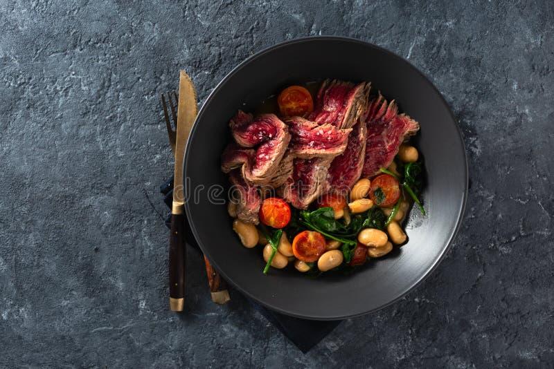 Placa de jantar com bife com feijão branco, espinafre e tomate, visão de fundo de pedra escura com coco livre fotos de stock royalty free