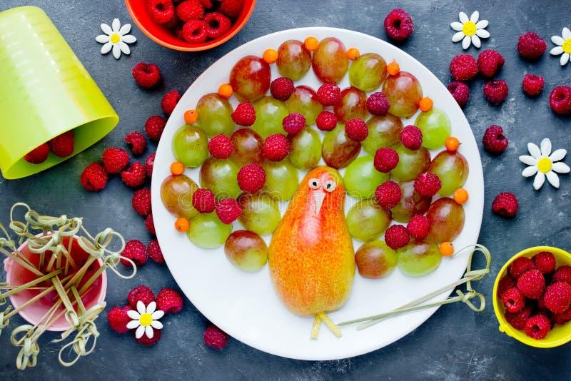 Placa de la baya de la fruta del pavo real, ensalada de fruta colorida del pavo real de la pera, uvas y frambuesas fotografía de archivo