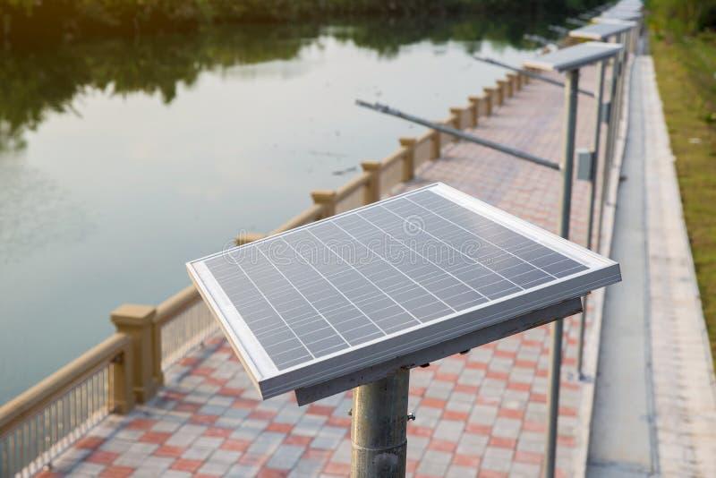 Placa de la célula solar en la manera del paseo al lado del río energía solar para convertido a la energía eléctrica fotografía de archivo