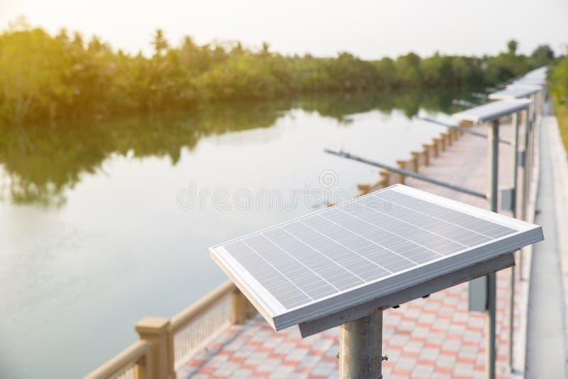Placa de la célula solar en la manera del paseo al lado del río energía solar para convertido a la energía eléctrica fotos de archivo libres de regalías