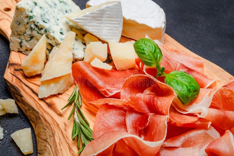 Placa de la carne del crudo italiano del prosciutto o jamon y queso españoles foto de archivo libre de regalías
