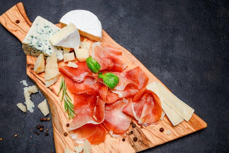 Placa de la carne del crudo italiano del prosciutto o jamon y queso españoles imágenes de archivo libres de regalías