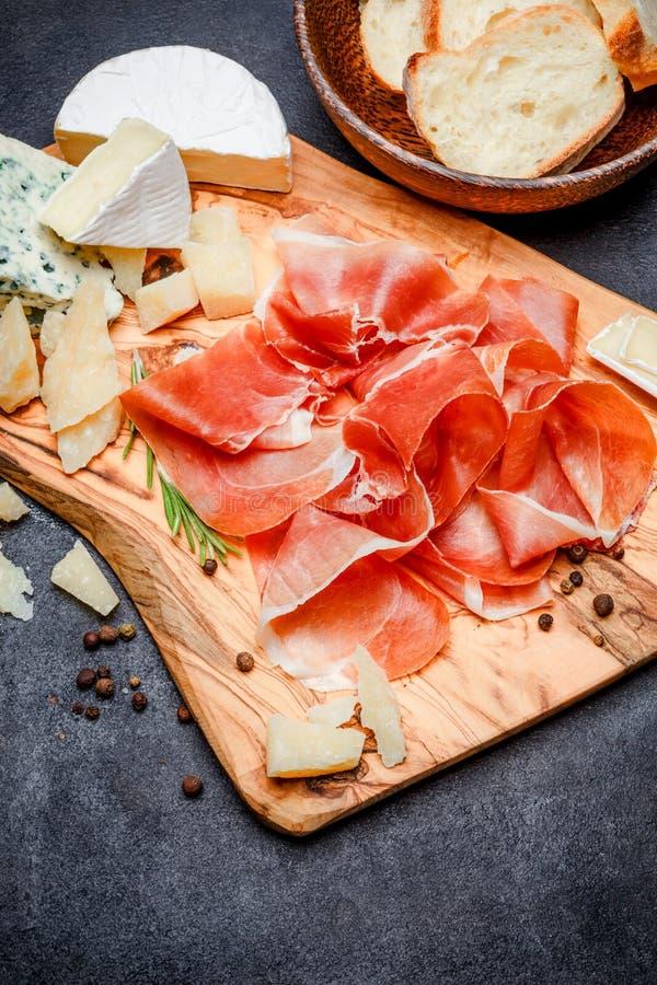 Placa de la carne del crudo italiano del prosciutto o jamon y queso españoles fotografía de archivo