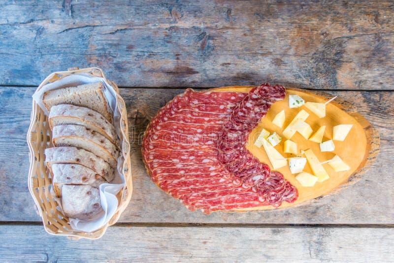 Placa de la carne fría en tabla de cortar en fondo de madera fotos de archivo