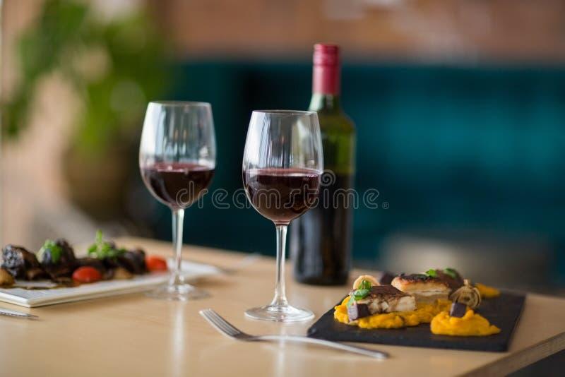 Placa de la comida con el vidrio de vino rojo foto de archivo