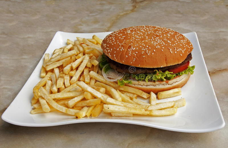 Placa con las fritadas y la hamburguesa imagenes de archivo