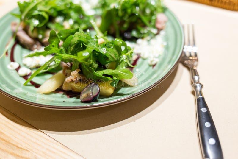 Placa de la ensalada fresca servida en la tabla en restaurante fotos de archivo
