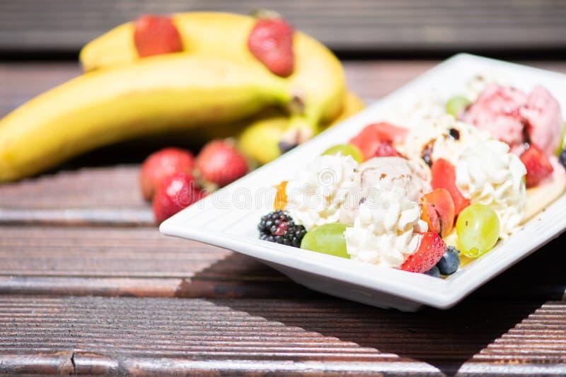 Placa de la ensalada de fruta fresca sana con helado en el fondo de madera fotos de archivo