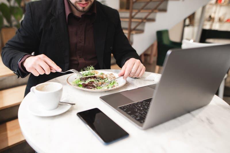 Placa de la ensalada, un ordenador portátil, una taza de café, un smartphone en la tabla en el restaurante fotos de archivo