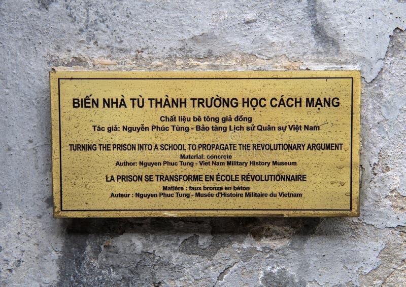 Placa de la información para el alivio de bronce en la prisión de Hoa Lo que conmemora dando vuelta a la prisión en una escuela foto de archivo