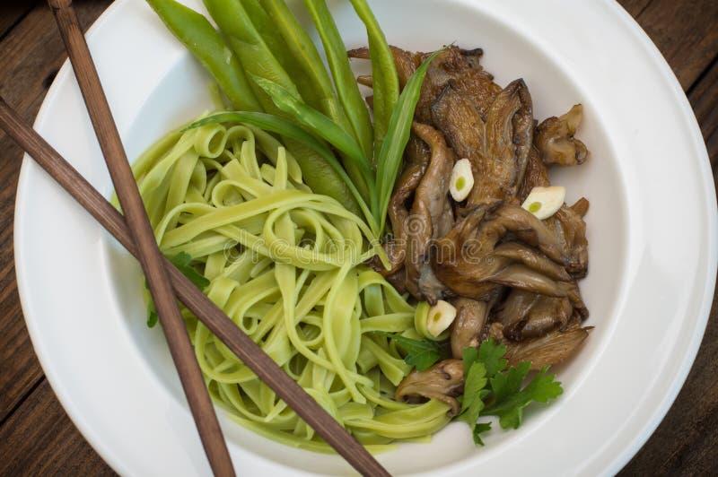 Placa de la pasta de los espaguetis con las setas de la espinaca y de ostra Cocina italiana, recetas italianas Fondo de madera Vi foto de archivo