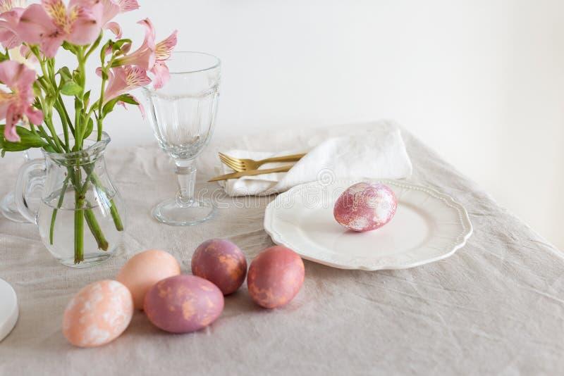 Placa de la porción de Pascua con los huevos de Pascua, el vajilla del oro, el vidrio y las flores rosados en el mantel de lino p fotos de archivo libres de regalías