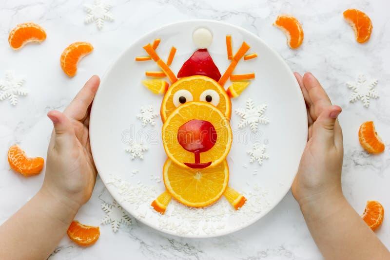 Placa de la tenencia del niño con el reno de la fruta comestible imagen de archivo