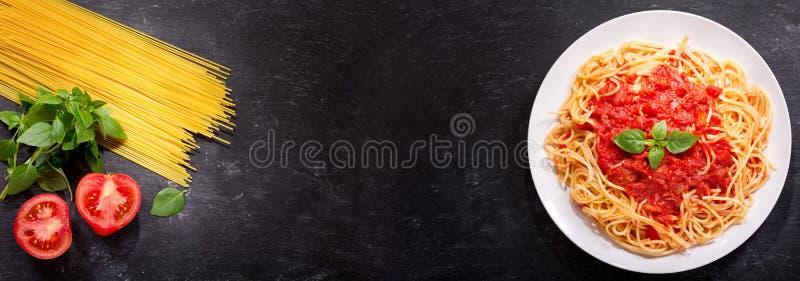 Placa de las pastas con la salsa y los ingredientes de tomate para cocinar imagenes de archivo