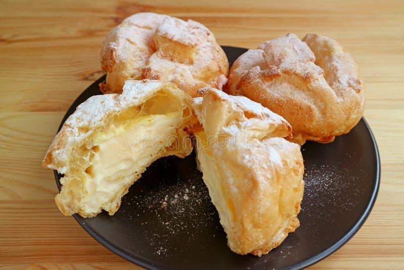 Placa de los soplos poner crema franceses llenados de crema o de Choux de las natillas pasteles de una nata del la servidos en la foto de archivo libre de regalías