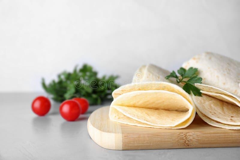 Placa de madeira com as tortilhas de milho na tabela P?o ?zimo imagem de stock royalty free