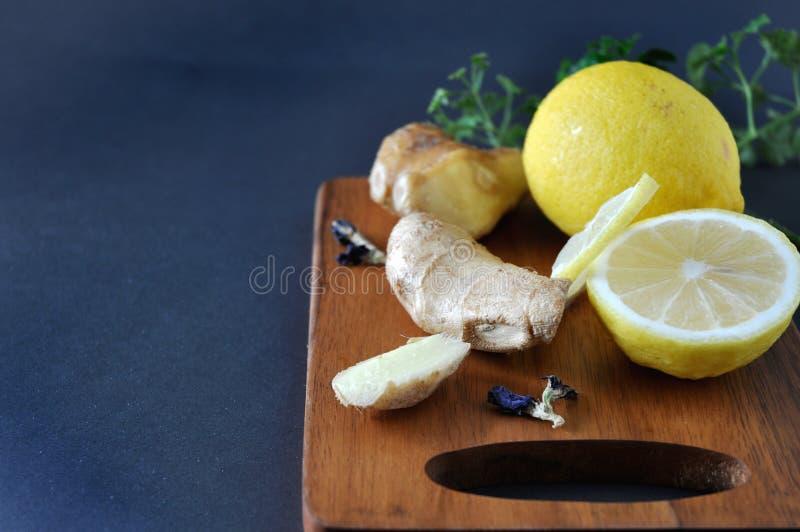 Placa de madeira com gengibre e o limão frescos fotografia de stock royalty free