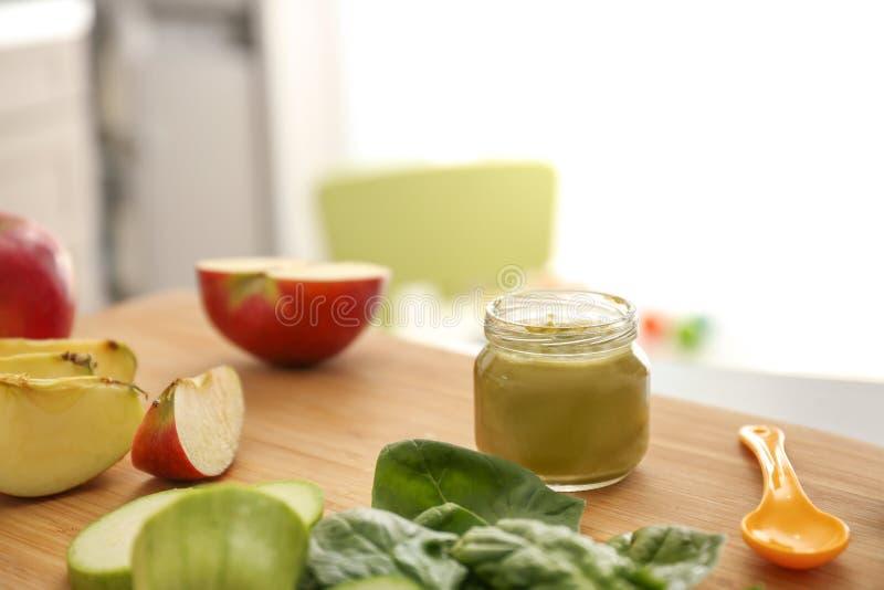Placa de madeira com os ingredientes para o comida para bebê na mesa de cozinha fotografia de stock