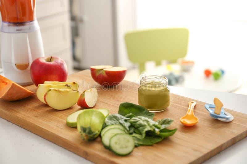 Placa de madeira com os ingredientes para o comida para bebê na mesa de cozinha imagens de stock