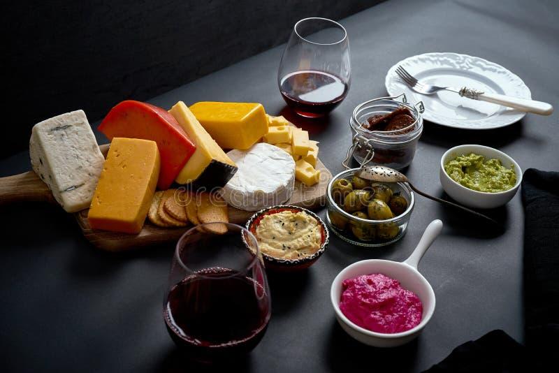 Placa de madeira com vários tipos de queijo e petiscos e dois vidros do vinho tinto na tabela preta fotografia de stock royalty free