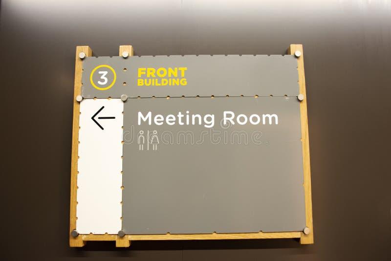 Placa de madeira ou etiqueta de madeira para o guia direto para ir para dentro à sala de reunião do prédio de escritórios imagem de stock