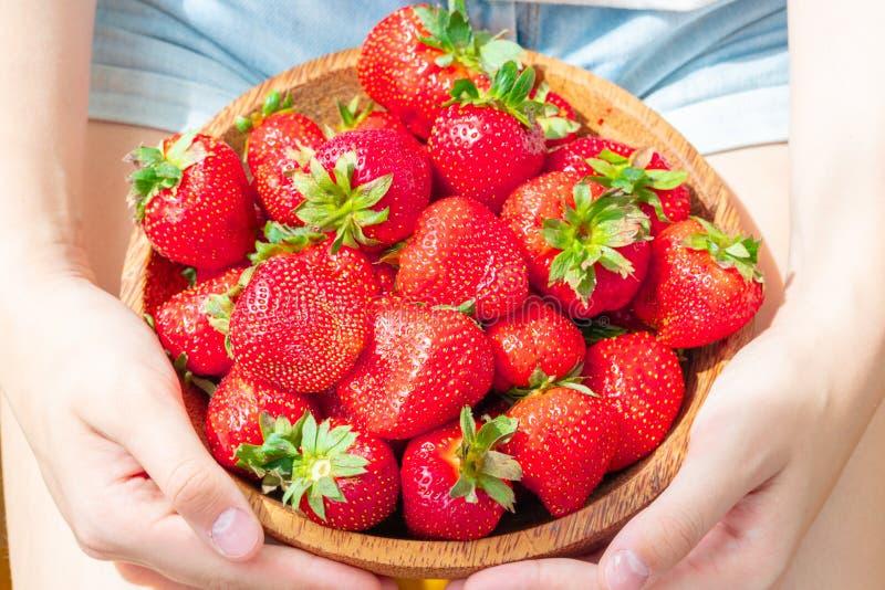 Placa de madera con las fresas en mano de la muchacha en fondo ligero imagen de archivo libre de regalías