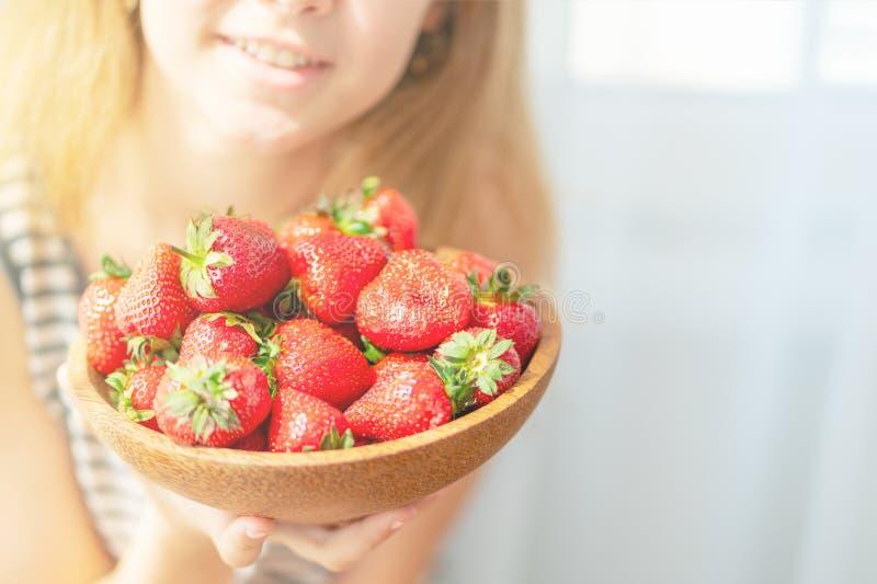 Placa de madera con las fresas en mano de la muchacha en fondo ligero imagenes de archivo