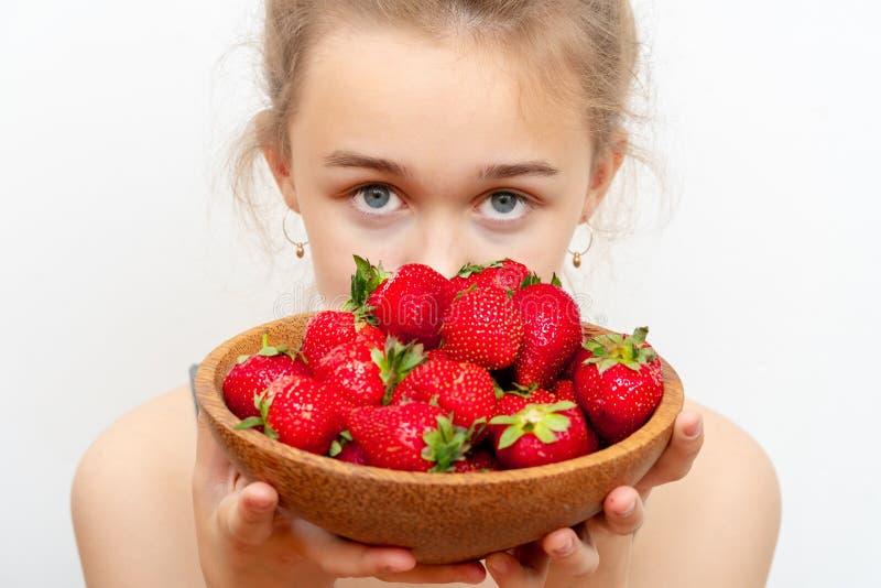 Placa de madera con las fresas en mano de la muchacha en fondo ligero foto de archivo libre de regalías