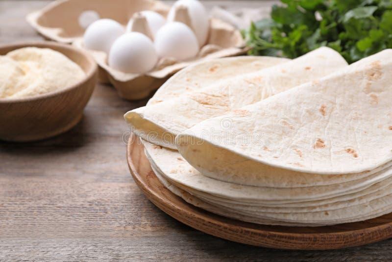 Placa de madera con las tortillas de maíz en la tabla Pan ?cimo fotografía de archivo